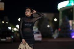 La muchacha morena presenta contra la ciudad de igualaci?n de la noche, las luces coloridas ilumina las ventanas que hacen compra fotografía de archivo libre de regalías