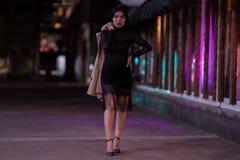 La muchacha morena presenta contra la ciudad de igualaci?n de la noche, las luces coloridas ilumina las ventanas que hacen compra imagen de archivo