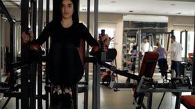 La muchacha morena sacude sus músculos abdominales, apoyando el cuerpo en el aire, llevando a cabo sus manos en la barra horizont metrajes