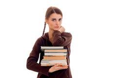 La muchacha morena seria elegante del estudiante con las coletas en deportes marrones viste con los libros en sus manos que miran Fotografía de archivo