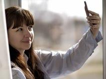 La muchacha morena sonriente joven en una camisa azul hace el selfie por la ventana imagen de archivo