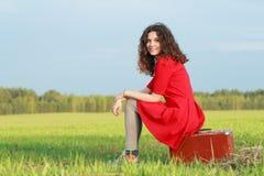 La muchacha morena sonriente se está sentando en la maleta de cuero vieja en el borde del campo de granja de la primavera Imagen de archivo libre de regalías