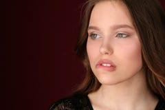 La muchacha muerde su labio Cierre para arriba Fondo rojo oscuro Imagen de archivo