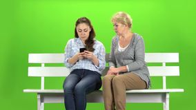 La muchacha muestra algo en el teléfono a su madre Pantalla verde almacen de metraje de vídeo