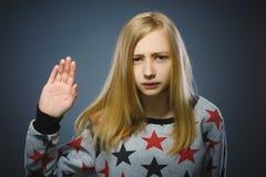 La muchacha muestra el brazo de la parada en fondo gris Fotos de archivo