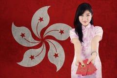 La muchacha muestra el sobre con la bandera de Hong Kong Fotos de archivo libres de regalías