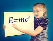 La muchacha muestra la fórmula escrita en un tablero plástico Fotos de archivo libres de regalías