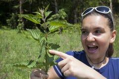 La muchacha muestra las hojas de la ortiga tacaña Imágenes de archivo libres de regalías