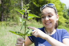 La muchacha muestra las hojas de la ortiga tacaña Imagen de archivo libre de regalías