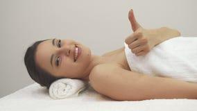 La muchacha muestra su pulgar para arriba en la tabla del masaje almacen de metraje de vídeo