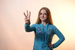 La muchacha muestra tres Fotos de archivo libres de regalías