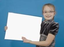 La muchacha muestra a un tablero plástico blanco Fotografía de archivo libre de regalías
