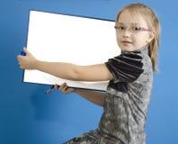 La muchacha muestra a un tablero plástico blanco Foto de archivo libre de regalías