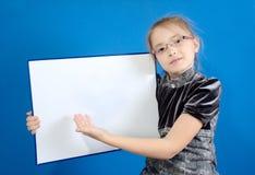 La muchacha muestra a un tablero plástico blanco Imágenes de archivo libres de regalías