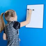 La muchacha muestra a un tablero plástico blanco Fotos de archivo libres de regalías