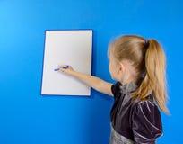 La muchacha muestra a un tablero plástico blanco Fotos de archivo