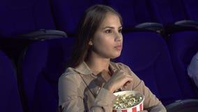 La muchacha muestra una muestra del silencio que se sienta en el pasillo del cine almacen de video