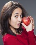 La muchacha multi-étnica juguetona 20s que sostiene una manzana para el placer en la consumición da fruto Fotos de archivo libres de regalías