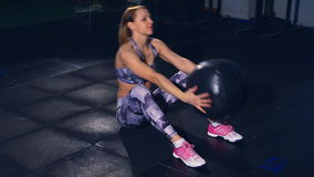 La muchacha muscular hermosa en medias apretadas grises se sienta sube con el tiro de la bola de medicina Ajuste de la cruz metrajes