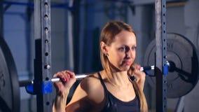 La muchacha muscular hermosa en ropa de deportes negra comienza a hacer sentar-UPS con un barbell en el gimnasio Front View metrajes