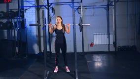 La muchacha muscular hermosa en ropa de deportes negra comienza a hacer sentar-UPS con un barbell en el gimnasio Front View almacen de video