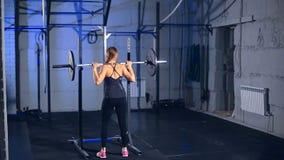 La muchacha muscular hermosa en ropa de deportes negra comienza a hacer sentar-UPS con un barbell en el gimnasio Visión posterior almacen de metraje de vídeo