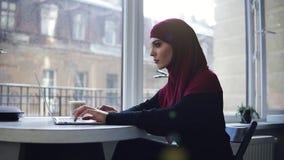 La muchacha musulmán atractiva con el hijab que cubre su cabeza es que considera y sonriente algo en su pantalla del ordenador po metrajes