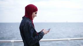 La muchacha musulmán atractiva joven con el hijab en su cabeza es de enrollamiento y que mecanografía algo en su smartphone mient almacen de video