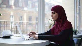 La muchacha musulmán atractiva joven con el hijab que cubre su cabeza está mecanografiando algo en su ordenador portátil mientras metrajes
