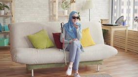 La muchacha musulmán ciega hermosa con un bastón en hijab en casa, goza del smartphone que se sienta en el sofá almacen de video
