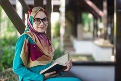 La muchacha musulmán con los vidrios y la tenencia del velo abrió el libro en el parque Foto de archivo