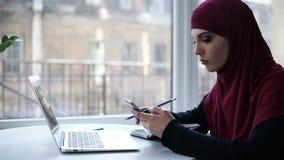 La muchacha musulmán de los jóvenes supuesto con el hijab púrpura en su cabeza escribe algo abajo de su smartphone, sentándose en almacen de metraje de vídeo