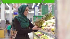 La muchacha musulmán en hijab en el supermercado elige una piña metrajes