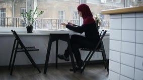 La muchacha musulmán hermosa con el hijab en su cabeza, sentándose cerca de la ventana, está mecanografiando abajo algo en el tec almacen de video