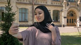 La muchacha musulmán hermosa joven en hijab está haciendo el selfie en su smartphone, mostrando como firma adentro d3ia en el ver almacen de metraje de vídeo