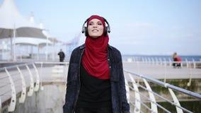 La muchacha musulmán moderna con el hijab que cubre su cabeza pone los auriculares y comienza a caminar en alguna parte gozando y almacen de metraje de vídeo