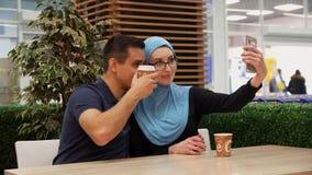La muchacha musulmán y el hombre joven se están divirtiendo que hace selfies en el teléfono almacen de metraje de vídeo