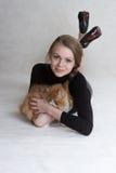 La muchacha muy bonita sostiene un gatito rojo Fotos de archivo libres de regalías