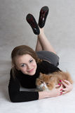 La muchacha muy bonita sostiene un gatito rojo Foto de archivo libre de regalías