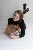 La muchacha muy bonita sostiene un gatito rojo Fotos de archivo