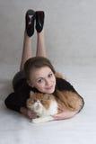La muchacha muy bonita sostiene un gatito rojo Foto de archivo