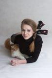 La muchacha muy bonita sostiene un gatito rojo Imagenes de archivo