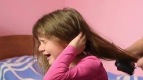 La muchacha muy está dañada cuando la mamá se peina el pelo enredado metrajes