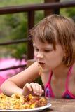 La muchacha muy hambrienta come el pollo asado a la parrilla Fotos de archivo