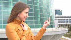 La muchacha muy hermosa está invitando para venir en la cámara al aire libre en la ciudad metrajes