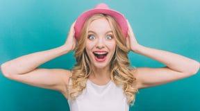 La muchacha muy salida está pareciendo directa y está sosteniendo sombrero rosado con las manos en una cabeza Mucho la sorprenden Fotografía de archivo libre de regalías