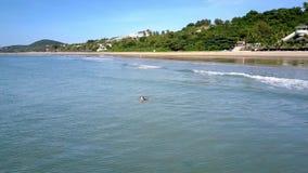 La muchacha nada en olas oceánicas tranquilas contra Palm Beach