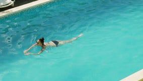 La muchacha nada en la piscina al aire libre en el hotel en un traje de baño negro almacen de video
