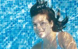 La muchacha nada en la piscina subacuática, adolescente activo feliz se zambulle y se divierte bajo el agua, la aptitud del niño  Foto de archivo