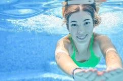 La muchacha nada en la piscina subacuática, adolescente activo feliz se zambulle y se divierte debajo del agua, aptitud del niño  Imagen de archivo